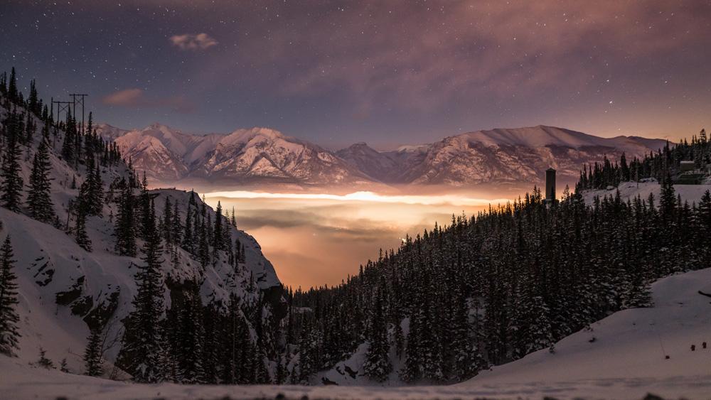 An inversion dances beneath Alberta dark skies in Canmore, Alberta